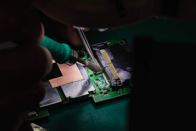 Close-up of man soldering chip on mobile phone in repair centre — Stock Photo