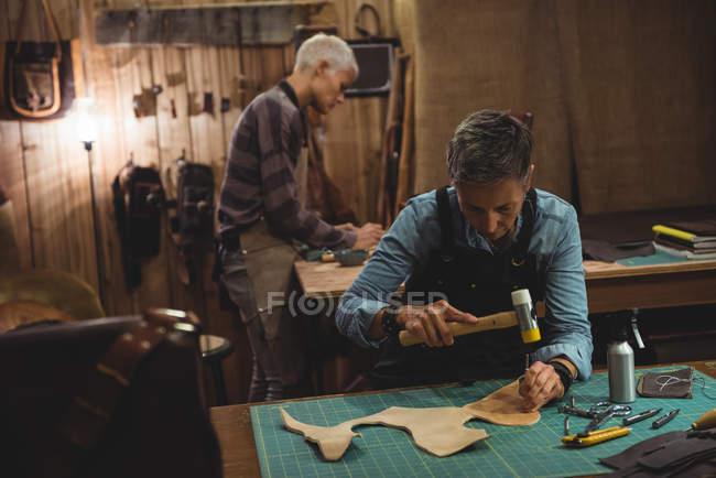 Maduro artesão martelando couro na oficina — Fotografia de Stock