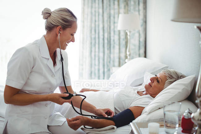 Nurse checking blood pressure of senior woman at home — Stock Photo