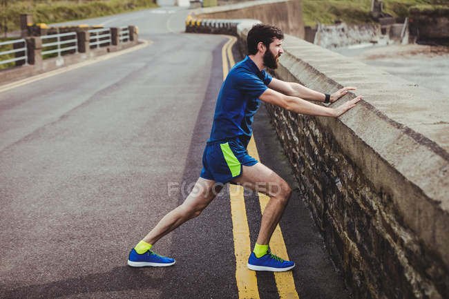 Handsome man performing stretching exercise at countryside — Stock Photo