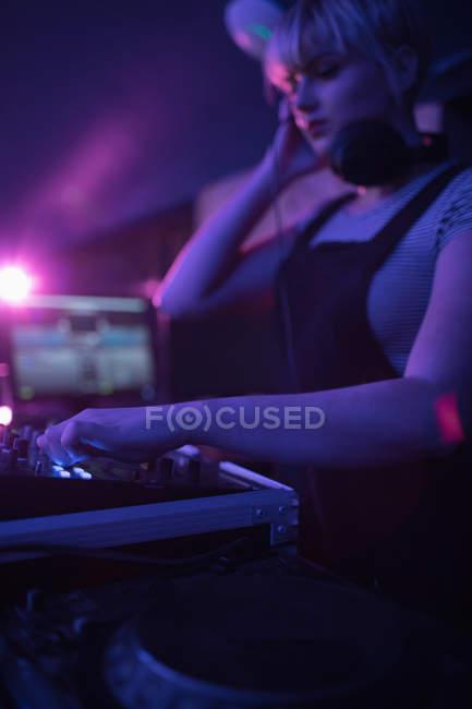 Femmina dj ascoltare le cuffie durante la riproduzione di musica nel bar — Foto stock