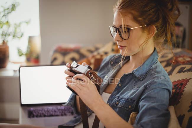 Mulher bonita olhando para fotos na câmera digital em casa — Fotografia de Stock