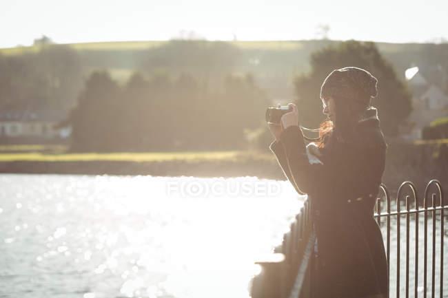 Mulher tirando fotos na câmera digital em um dia ensolarado no parque — Fotografia de Stock