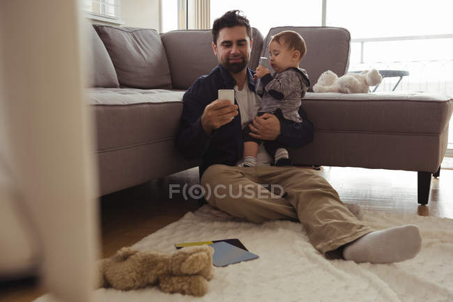 Father holding his baby while using mobile phone at home — Stock Photo