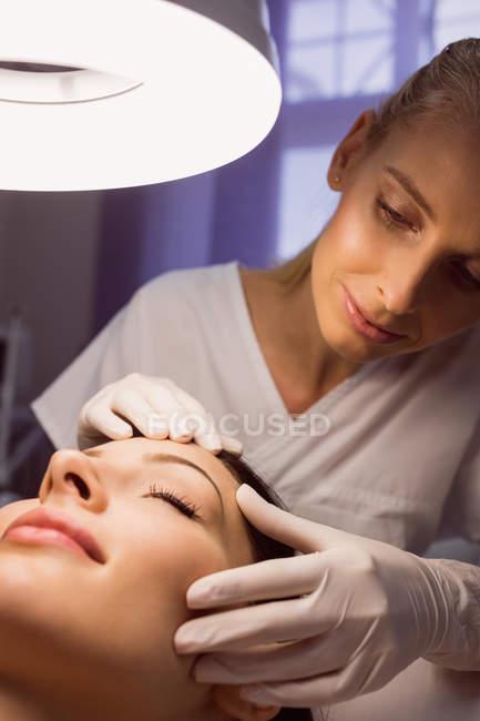 Dermatologe untersucht weibliche Patientenhaut in Klinik — Stockfoto