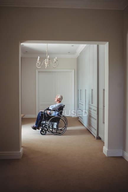 Senior Mann sitzt im Rollstuhl zu Hause — Stockfoto