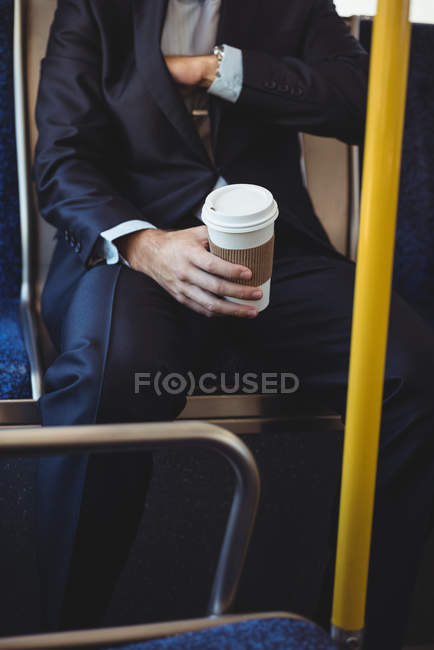 Mid section of a businessman with disposable coffee cup checking blazer pocket while travelling in bus — Stock Photo