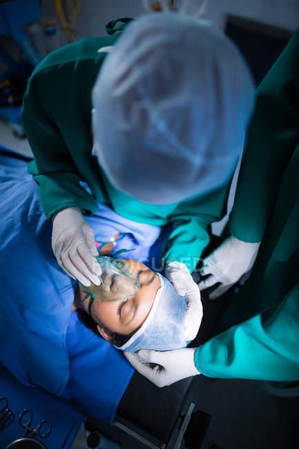 Chirurgen richten Sauerstoffmaske auf Patient im Operationssaal des Krankenhauses ein — Stockfoto
