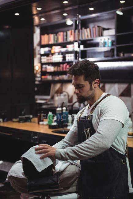 Barbier essuyant visage client avec serviette chaude dans le salon de coiffure — Photo de stock