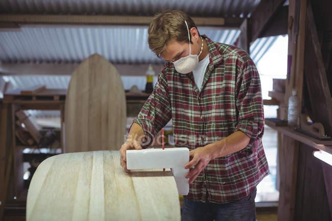Человек с маркировкой на доске для серфинга в мастерской — стоковое фото