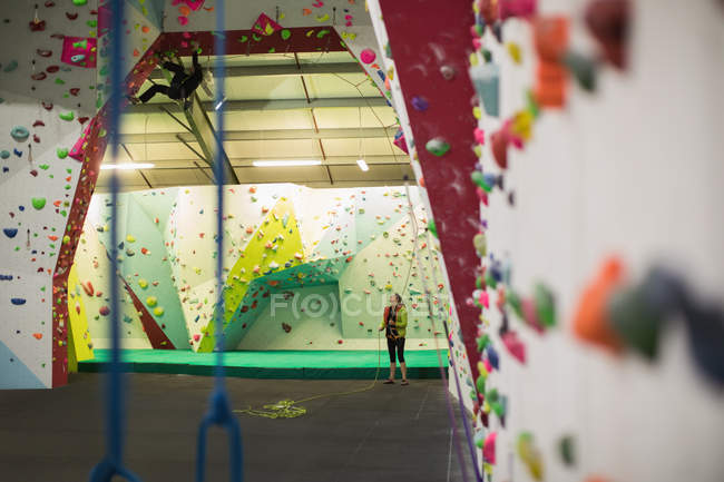 Hombre practicando escalada en roca con entrenador en pared de escalada artificial en gimnasio - foto de stock