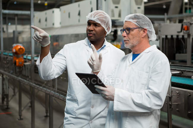Male workers inspecting products in cold drink factory - foto de stock