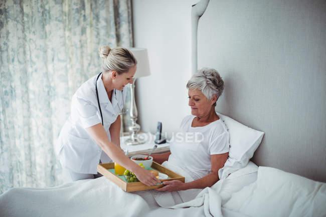Arzt serviert Seniorin Frühstück im Schlafzimmer — Stockfoto