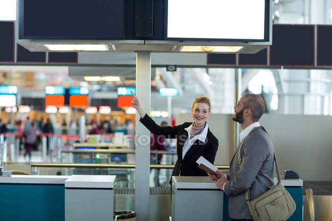 Airline check-in attendant showing direction to commuter at check-in counter in airport terminal - foto de stock