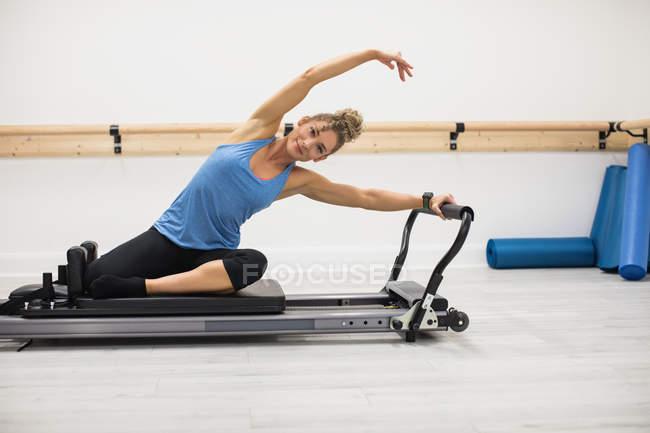 Женщина тренируется на реформаторском оборудовании в тренажерном зале — стоковое фото