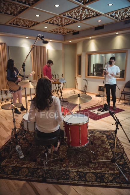 Music band performing in a recording studio — Stock Photo