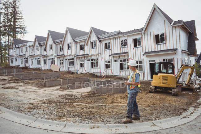 Trabalhador da construção segurando tablet digital no canteiro de obras — Fotografia de Stock