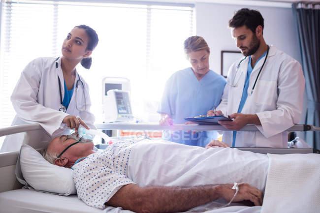 Doctora, poner mascarilla de oxígeno en cara de paciente en el hospital - foto de stock