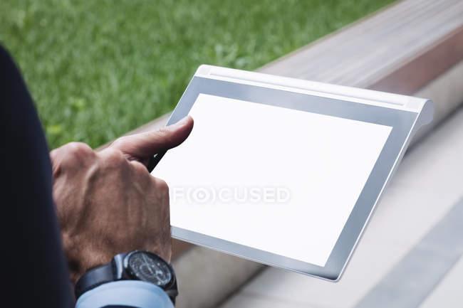 Обітнутого зображення бізнесмен, використовуючи цифровий планшетний за межами Офісна будівля — стокове фото