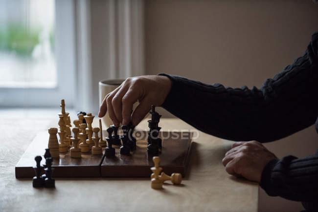 Средняя часть мужчины играет в шахматы дома — стоковое фото