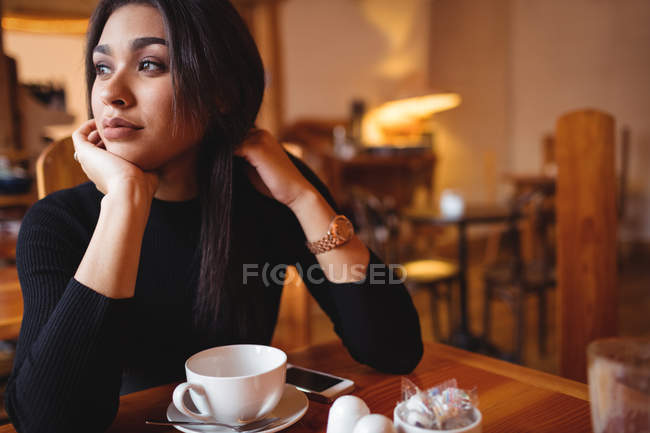 Thoughtful woman sitting in coffee shop — Stock Photo