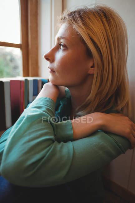 Женщина смотрит в окно дома — стоковое фото