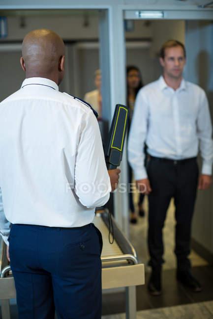 Аеропорт офіцер безпеки стоячи з металошукачем перевірити пасажирських перевезень в аеропорту — стокове фото