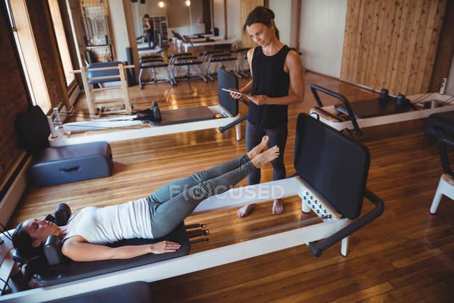 Formateur en aidant la femme avec tablette numérique tout en pratiquant le pilates en studio de remise en forme — Photo de stock
