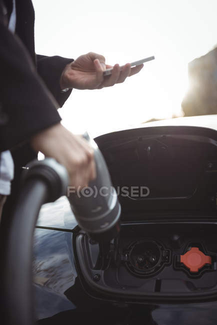 Mid section of man using mobile phone while charging car at electric vehicle charging station — Stock Photo
