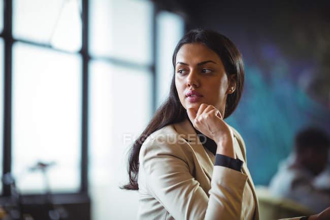 Продуманий бізнес-леді фотографіях хтось дивитися вбік в офісі — стокове фото