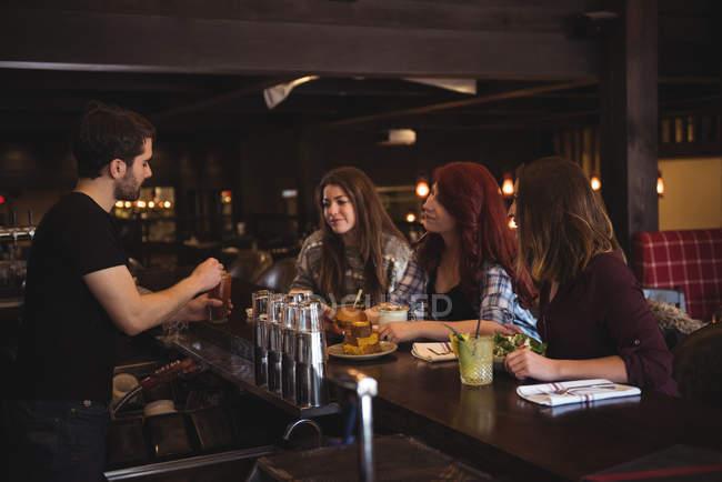 Друзів насолоджуватися напоями в барна стійка під час приготування коктейлів бармена — стокове фото
