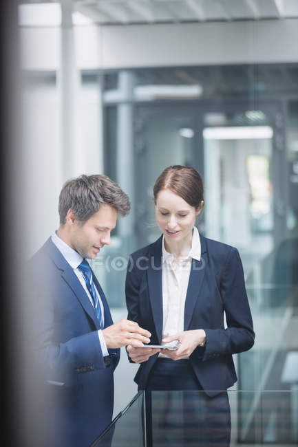 Бизнесмен и коллега, обсуждая над цифровой планшетный внутри офисного здания — стоковое фото