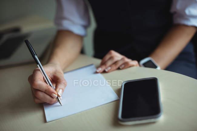 Бізнес-леді писати блокнот в офісі — стокове фото