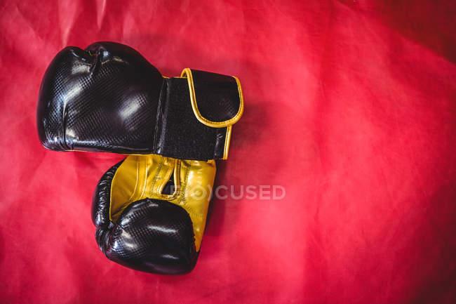 Coppia di guanti da boxe sulla superficie rossa in palestra — Foto stock