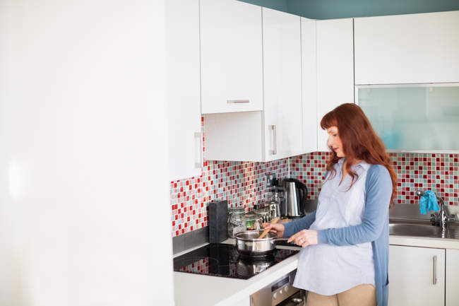 Pregnant woman cooking food in kitchen at home — Stock Photo