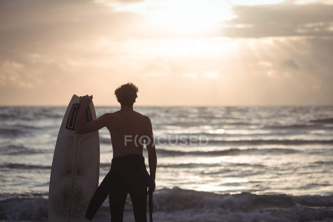 Rear view of a man carrying surfboard standing on beach at dusk — Stock Photo