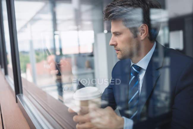 Homme d'affaires à l'aide de téléphone portable et tasse à café jetable tenue au bureau — Photo de stock