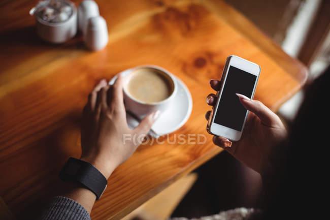 Donna che utilizza il telefono cellulare mentre prende una tazza di caffè al caffè — Foto stock
