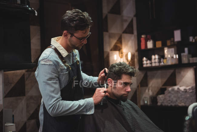 Customer getting hair trimmed with razor in barber shop — Stock Photo