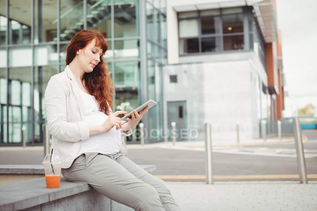 Pregnant businesswoman using digital tablet in office premises — Stock Photo