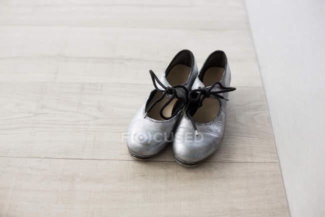 Pair of dancing shoes on wooden floor in dance studio — Stock Photo
