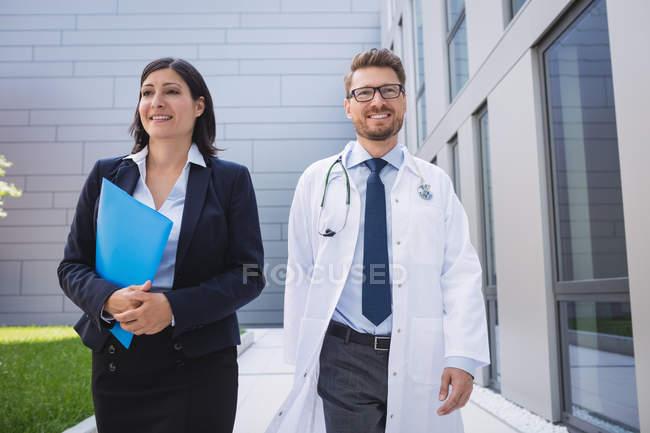 Medici sorridenti che camminano insieme nei locali ospedalieri — Foto stock