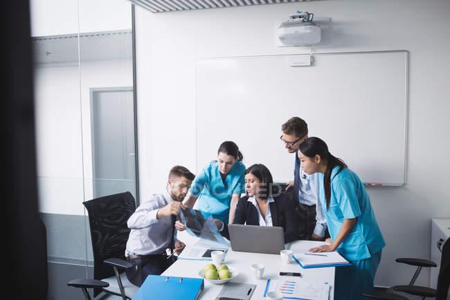 Equipo médico examinando un informe de rayos x en la sala de conferencias - foto de stock