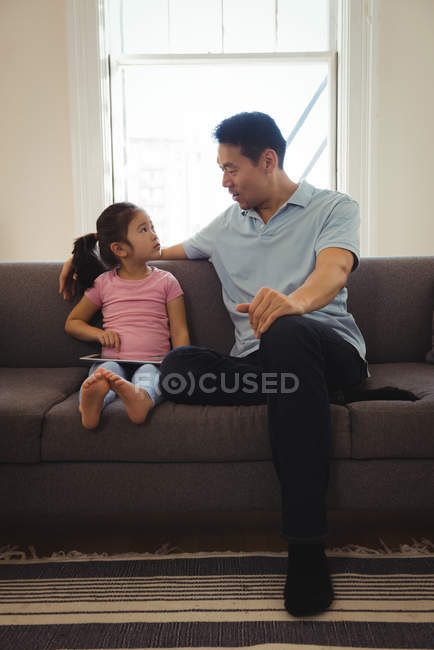 Father and daughter interacting while using digital tablet in living room at home - foto de stock