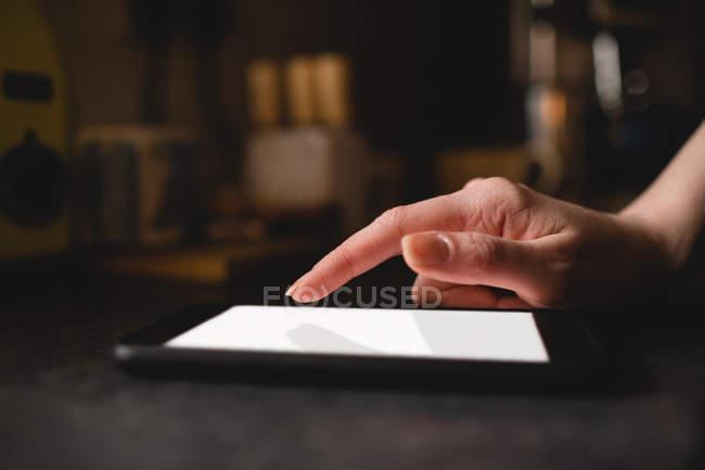 Mano della donna utilizzando tablet digitale in cucina a casa — Foto stock