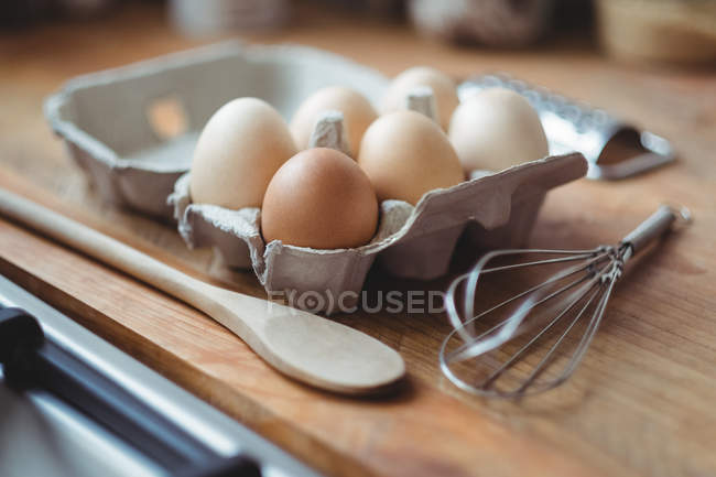 Eggs, whisker and wooden spoon on table in kitchen — Stock Photo