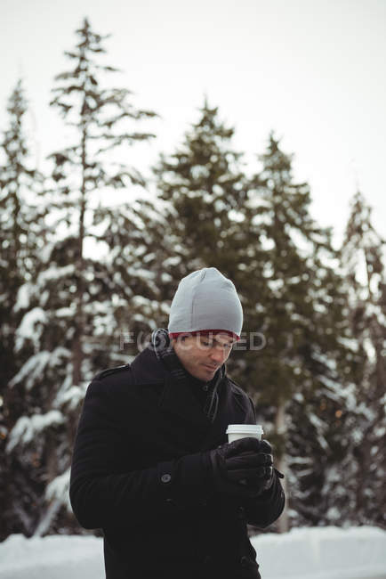 Man in warm clothing holding coffee cup during winter — Stock Photo