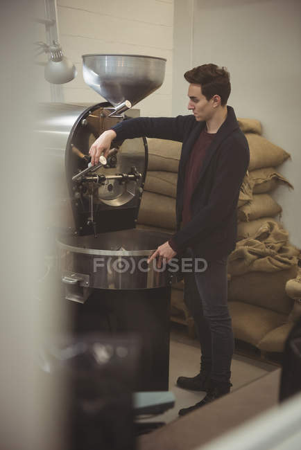 Man operating coffee roasting machine in coffee shop — Stock Photo