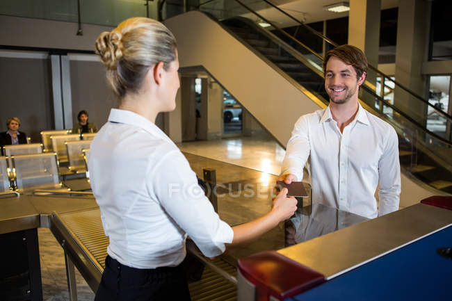 Funcionários do sexo femininos dando embarque passam para o cheque no balcão do Aeroporto terminais — Fotografia de Stock