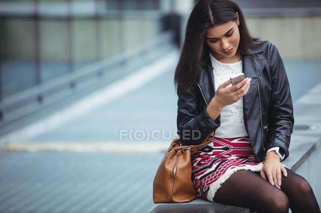 Женщина, использующая мобильный телефон возле офисного здания — стоковое фото